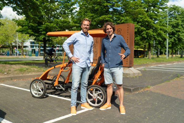 Frans van Leeuwen en Tijs Koedam voor de oranje fiets, pratend over vitaliteit en hoe je een vitaliteitsbeleid een succes maakt