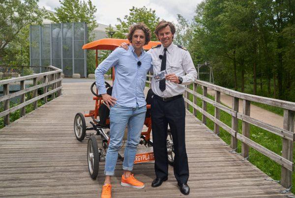 Tijs en Berend op een brug in Utrecht, staand voor de oranje fiets en pratend over vitale medewerkers