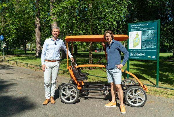 Frank en Tijs voor de oranje fiets, pratend over verandermanagement