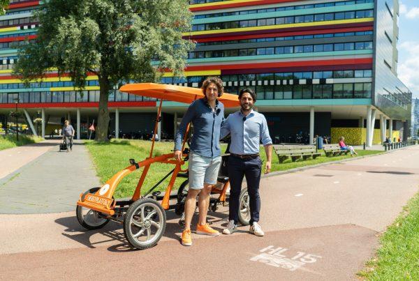 Tijs en Fabio voor de oranje fiets pratend over bewegen en stress