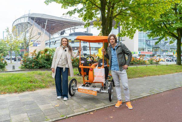 Sabine en Tijs voor de oranje fiets, pratend over stress verminderen door altijd een dokter op zak te hebben